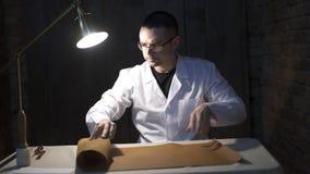 Trabalhador de couro que olha o material de couro na tabela Opinião superior o artesão que trabalha com couro Opinião de ângulo a video estoque