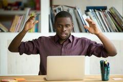 Trabalhador de escritório afro-americano chocado que olha a tela do portátil fotos de stock