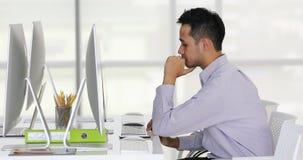 Trabalhador de escritório asiático que boceja e que datilografa video estoque