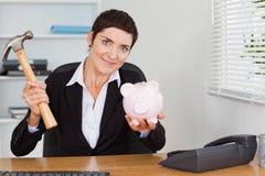 Trabalhador de escritório bonito que quebra um piggybank fotos de stock