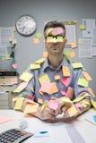 Trabalhador de escritório coberto com as notas da vara Fotografia de Stock Royalty Free