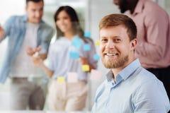 Trabalhador de escritório deleitado positivo que está no local de trabalho imagens de stock royalty free