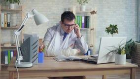 Trabalhador de escritório do homem com um braço quebrado que fala no telefone vídeos de arquivo