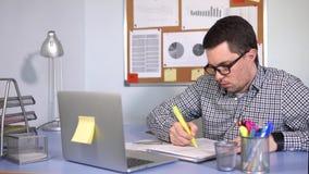 Trabalhador de escritório em seu escritório no trabalho ele que trabalha com papéis vídeos de arquivo