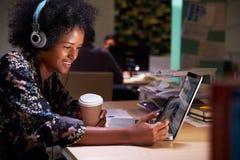 Trabalhador de escritório fêmea com café na mesa que trabalha tarde foto de stock royalty free
