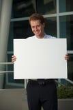 Trabalhador de escritório feliz atrás do vertical em branco do sinal Fotografia de Stock Royalty Free