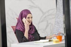 Trabalhador de escritório islâmico fêmea esperto moderno que fala no telefone Fotos de Stock