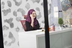 Trabalhador de escritório islâmico fêmea esperto moderno que fala no telefone Imagens de Stock