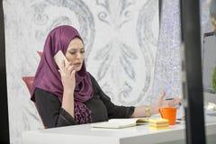 Trabalhador de escritório islâmico fêmea esperto moderno que fala no telefone Imagem de Stock Royalty Free
