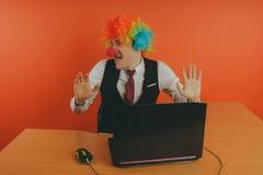Trabalhador de escritório na peruca do palhaço, conceito do palhaço no trabalho fotografia de stock