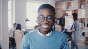 Trabalhador de escritório novo afro-americano feliz nos vidros que olha fixamente na câmera 4K de levantamento e de sorriso do de filme