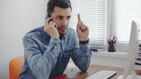 Trabalhador de escritório novo que disca um número e que fala em seu telefone celular no escritório que senta-se na tabela com co vídeos de arquivo