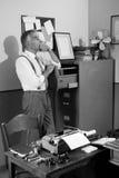 Trabalhador de escritório pensativo que procura um arquivo no armário Imagens de Stock