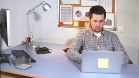 Trabalhador de escritório, que é ocupado texto datilografar em um portátil do portátil usando o Internet video estoque