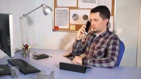 Trabalhador de escritório que fala em um telefone celular com seu cliente que senta-se em seu escritório vídeos de arquivo