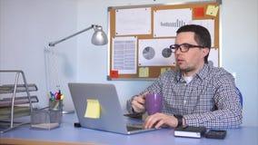 Trabalhador de escritório que olha o chá bebendo do monitor ao imprimir o texto no portátil filme