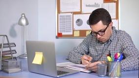 Trabalhador de escritório que trabalha no portátil e que redige para baixo a informação nos papéis filme
