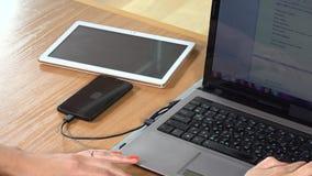Trabalhador de escritório que usa o computador e o telefone esperto prendido que carregam na tabela closeup filme