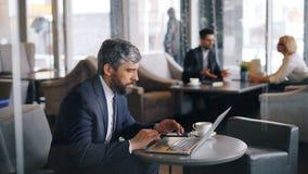 Trabalhador de escritório que usa o portátil no café que senta-se na tabela e datilografando o trabalho apenas vídeos de arquivo