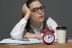 Trabalhador de escrit?rio cansado na tabela com pap?is e o despertador vermelho fotografia de stock