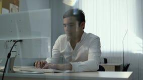 Trabalhador de escrit?rio que datilografa no teclado O indivíduo traz pensativamente sua mão a seu queixo video estoque