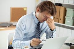 Trabalhador de escritório cansado que toca em sua ponte do nariz para dar o resto a Imagem de Stock Royalty Free