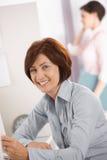 Trabalhador de escritório fêmea maduro de sorriso Fotografia de Stock