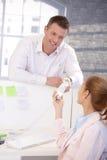 Trabalhador de escritório masculino que passa o telefone ao colega Fotografia de Stock