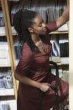 Trabalhador de escritório na escada na sala de armazenamento do arquivo Fotografia de Stock