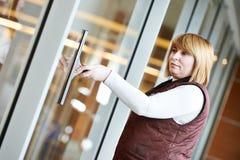 Trabalhador de mulher que limpa a janela interna Imagens de Stock Royalty Free