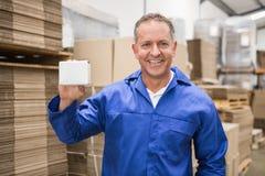 Trabalhador de sorriso do armazém que guarda a caixa pequena imagens de stock