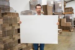 Trabalhador de sorriso do armazém que guarda o grande cartaz branco Imagem de Stock