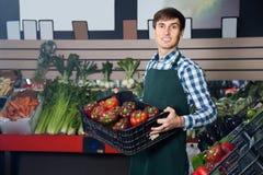 Trabalhador de sorriso do mantimento no mercado local Imagem de Stock Royalty Free