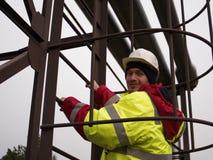 Trabalhador de sorriso feliz no capacete montanhista industrial em escadas de escalada do uniforme Fotografia de Stock