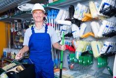 Trabalhador de sorriso no rolo de pintura de compra do capacete de segurança Imagem de Stock