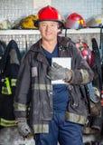 Trabalhador de sorriso que guarda a tabuleta de Digitas no fogo Imagens de Stock