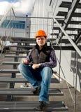 Trabalhador de sorriso que relaxa na escadaria do metal durante a ruptura fotos de stock