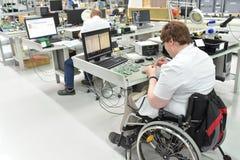 Trabalhador deficiente em uma cadeira de rodas que monta o compone eletrônico imagens de stock