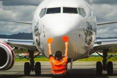 Trabalhador do aeroporto que dirige o avião de passageiros com pás Foto de Stock