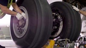 Trabalhador do aeroporto que verifica o chassi Motor e chassi do avião do passageiro sob a manutenção pesada Verificações do coor imagem de stock royalty free