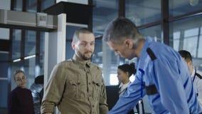 Trabalhador do aeroporto que verifica o passageiro com o detector de metais Fotos de Stock Royalty Free