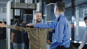 Trabalhador do aeroporto que verifica o passageiro com o detector de metais Imagem de Stock Royalty Free