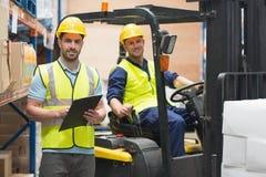 Trabalhador do armazém e motorista de sorriso da empilhadeira Imagens de Stock