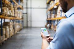 Trabalhador do armazém do homem com um smartphone imagens de stock royalty free