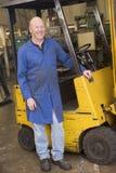 Trabalhador do armazém que está pelo forklift Imagem de Stock Royalty Free