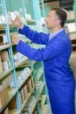 Trabalhador do armazém que toma o artigo encaixotado da prateleira fotografia de stock