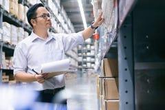 Trabalhador do armazém que verifica bens no armazém imagem de stock royalty free