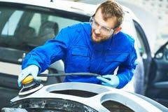 Trabalhador do auto mecânico que lustra o carro abundante Imagem de Stock