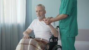 Trabalhador do centro de reabilitação que apoia o homem deficiente, recomendando para não dar acima video estoque