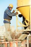 Trabalhador do construtor no derramamento concreto no formulário foto de stock